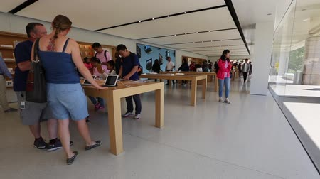 apple sign : Cupertino, CA, USA - August 15, 2016: people inside the popular Apple store of Apple Inc Headquarters at One Infinite Loop located in Cupertino, Silicon Valley, California. Stock Footage