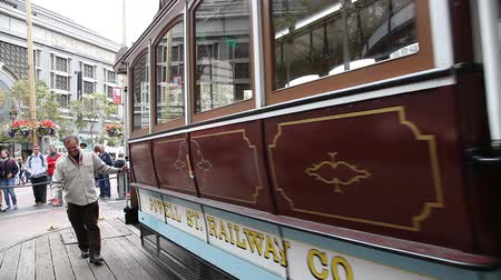 kabely : San Francisco, CA, USA - August 15, 2016: Cable car operators push the turntable around the reverse direction in Powell and Market St Turntable or terminus while crowds of tourists waiting to go up.