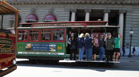フランシスコ : San Francisco, California, United States - August 17, 2016: Classic cable cars on wheels with guided tour carrying tourists in front of Westin St. Francis hotel along the famous Powell Street. 動画素材