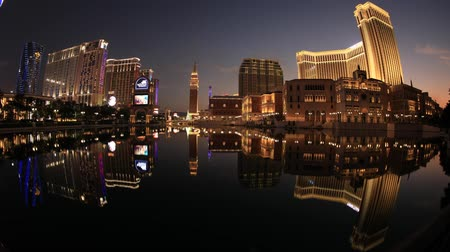 Вегас : Macau, China - December 8, 2016: sunset time lapse of The Venetian Macau mirroring on lake at twilight, the largest casino in the world and the largest single structure hotel building in Asia.