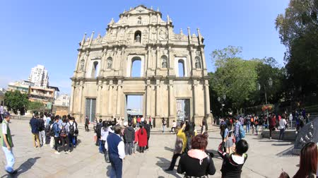 ikonik : Macau, China - December 8, 2016: tourists taking pictures and selfie on staircase of Ruins of St. Pauls in a sunny day. iconic stone facade, most popular historic attractions in Macau. Time lapse.