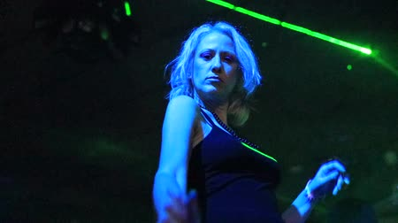 zmysłowy : Sensual modern dance in the dark of a discotheque under green laser strobe lights. Entertainment, leisure and nightlife concept. Adult lifestyle. Low angle view. Slow motion effect.