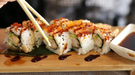 took : Uramaki of shrimp tempura, cheese, avocado and tobiko caviar dipped in soy sauce bowl. Japanese fusion food, Asian cultures. Healthy food, light diet concept. Slow motion effect on chopsticks. Stock Footage