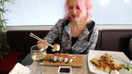 took : Glamour woman eating in slow motion a California Temaki cone with shrimp tempura, rice, avocado and seaweed, in soy sauce cup. In Japanese fusion Asian restaurant. Healthy food, light diet concept.
