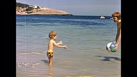 baleár : Ibiza, Spain - circa 1973: Two tourist children on holiday playing ball in the sea of the beach of Bay of Portinatx in 70s. Historical restored footage.