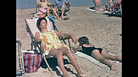 baleár : Ibiza, Spain - circa 1973: Tourist families on holiday sunbathing on the beach of Bay of Portinatx in 70s. Vintage restored footage. Stock mozgókép