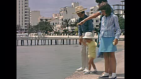 baleár : Ivissa, Ibiza, Spain - circa 1973: Vintage restored panorama of Ivissa port town in seventies. Tourist family visiting the harbour in typical 70s vintage clothing. Stock mozgókép