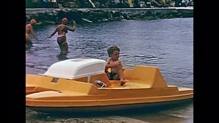 baleár : Ibiza, Spain - circa 1973: Tourist child on holiday playing on pedalo pedal boat in the sea of the beach of Bay of Portinatx in 70s. Historical restored footage.