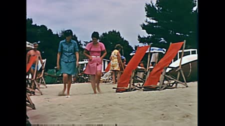 baleár : Ibiza, Spain - circa 1973: Two tourist women in vintage clothing playing with the sand on holiday on the beach of Bay of Portinatx in 70s. Vintage restored footage.