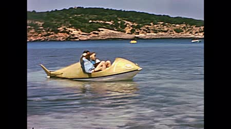 baleár : Ibiza, Spain - circa 1973: Vintage restored footage of holiday tourists family on whale pedal boat in typical 70s vintage swimsuit. Beach of Bay of Portinatx. Stock mozgókép