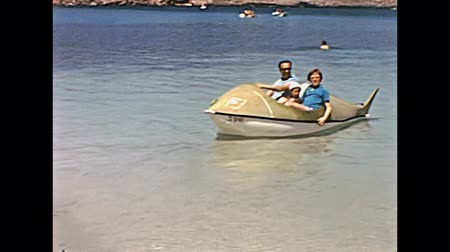 baleár : Ibiza, Spain - circa 1973: Tourists on holiday on typical whale pedal boat in the sea of the beach of Bay of Portinatx in 70s. Vintage restored footage. Stock mozgókép