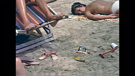 baleár : Ibiza, Spain - circa 1973: holiday families on the beach of Bay of Portinatx in 70s. Sunbathing, playing and reading newspaper in typical 70s vintage swimsuit. Historical restored footage.