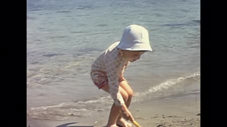 seventy : Malta island - circa 1970: Restored historical footage of a tourist little boy on holiday playing with the sand in the sea of the beach in 70s. Typical vintage clothing. Stock Footage