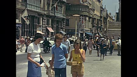 seventy : Malta island - circa 1970: Tourist family visiting the old town roads in typical vintage clothing. Historical restored footage. Stock Footage