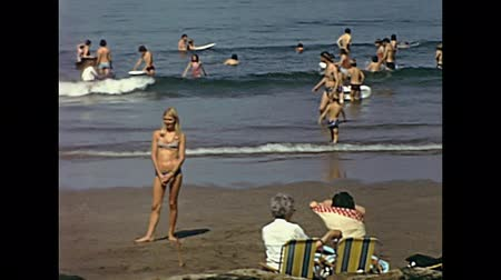 Мальта : Malta island - circa 1970: Tourist families on holiday sunbathing on the beach in seventies. Historical restored footage. Typical vintage swimsuit.
