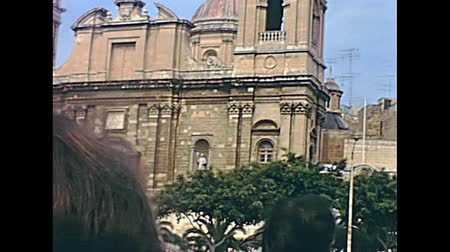maltština : Historical restored footage of Malta from 1970: Ancient Collegiate St Lawrence church, located in old fortified city Birgu. Main gate with bell towers sea level view from boat tour.