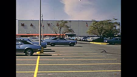 new clothes : Swansea, United States of America - circa 1970: Old footage of people and vintage cars in the parking lot of Macys Shop Fashion Clothing and Accessories, on Swansea Mall Drive in 70s. Stock Footage