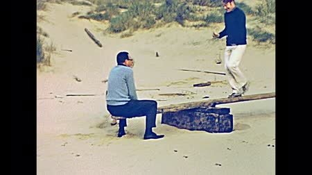 baleár : MAJORCA, SPAIN - circa 1970: Historical restored footage of tourist family on holiday on a Majorca beach in 70s. Playing with a seesaw in typical seventies clothes.