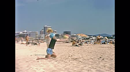 baleár : MAJORCA, SPAIN - circa 1970: Two tourist children on holiday playing ball on the beach of Cala Millor Playa in 70s. Historical restored footage. Summer holidays 70s concept. Stock mozgókép