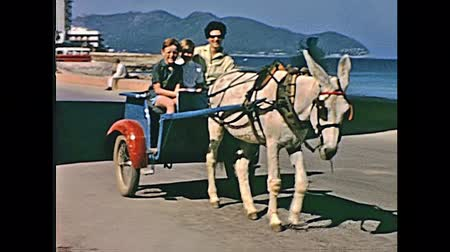 baleár : MAJORCA, SPAIN - circa 1970: horse carriage with a family on holiday visiting the waterfront coastline of Cala Millor Play in typical 70s vintage outfits. Historical restored footage.