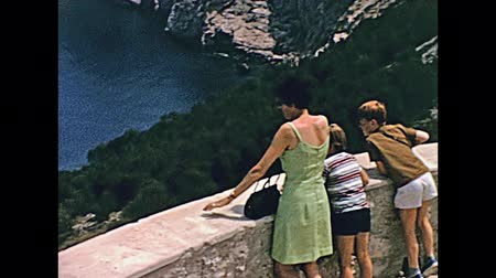 ações : MAJORCA, SPAIN - circa 1970: tourist family in typical 70s vintage dresses at Mirador de Es Colomer lookout. Majorca historical footage. Stock Footage