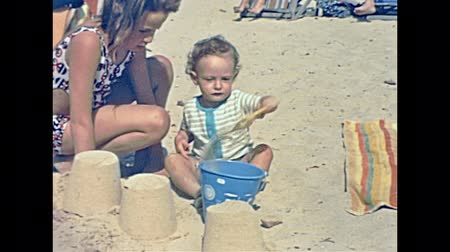 seventy : MAJORCA, SPAIN - circa 1970: children on holiday on the beach of Cala Millor Playa in 70s. playing with sand castles in typical 70s vintage swimsuit. Historical restored footage