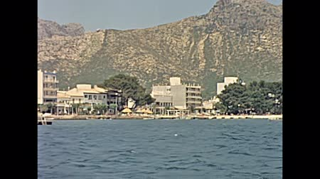 arquipélago : MAJORCA, SPAIN - circa 1970: families on holiday on boat tour, sunbathing and visiting Majorca island coast in typical 70s vintage style dresses. Historical restored footage.