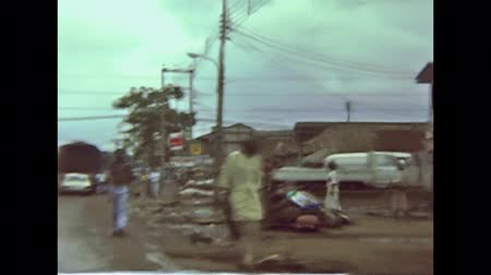 seventy : LAGOS, NIGERIA, AFRICA - 1976: Vintage historical footage driving on dirt roads of Lagos town with old houses and black Nigerian people walking in the street traffic. FPV from a Galant Mitsubishi car.