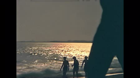 lagos : LAGOS, NIGERIA, AFRICA - 1976: black Nigerian people and white caucasian tourists having fun together on the Lagos beach at sunset. Atlantic Ocean of the Guinea gulf. Historical vintage footage. Stock Footage