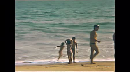 seventy : LAGOS, SOUTHERN NIGERIA, AFRICA - 1976: black Nigerian people and white caucasian tourists together on Lagos beach. Men,women and children swimming in the Atlantic Ocean. Typical 70s vintage swimsuit
