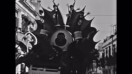 caracteres : Marghera, Italy - circa 1960: Chariot in traditional Venice carnival. Chariot with dog,flowers and bees characters. Historical restored footage.