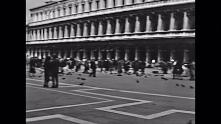 torre sineira : Venice, Italy - circa 1960: Historical restored footage of tourists in San Marco venetian square with San Marco Basilica and bell tower. Tourists in typical 60s clothes.