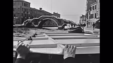 европейский : Historical boat tour on Cannaregio canal, person view of Bridge of Three Arches, one of the main bridges of Venice in Italy, Italian city of Unesco Heritage. Historical restored footage on 1960. Стоковые видеозаписи
