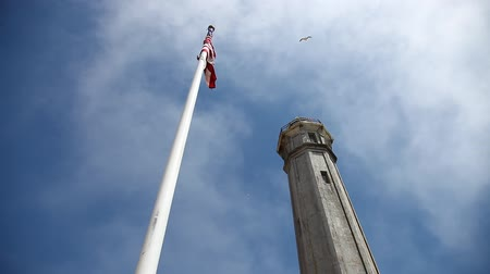 sas : San francisco prison Alcatraz in Eagle Plaza with American flag waving and lighthouse, ground view against moving cloudy sky, a fling bird. Concept of American freedom. Travel and holidays concept.