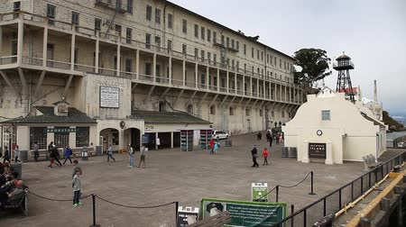 knihkupectví : San Francisco, United States - August 14, 2016: Alcatraz penitentiary sally port. Main building with guard tower, theater, ranger station and bookstore. Dock full of tourists waiting for boat. Dostupné videozáznamy
