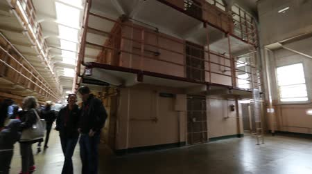 бронированный : San Francisco, United States - August 14, 2016: Alcatraz prison main room with three rows of cells on three levels. Many tourists visiting on tour every day. San Francisco historical landmark.