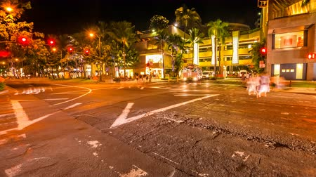 Оаху : HONOLULU, OAHU, HAWAII, USA - AUGUST 21, 2016: Time lapse at night of a Waikiki crossroad. People moving for shopping and car crossing. Cityscape night lights. Luxury, holidays and nightlife concept.