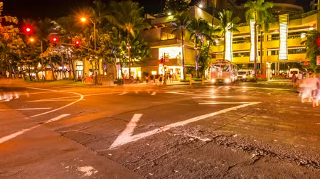 Оаху : HONOLULU, OAHU, HAWAII, USA - AUGUST 21, 2016: Moving time lapse at night in Waikiki street life at crossroad. People moving for shopping and car crossing. City night lights and nightlife concept.