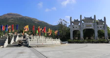 loajální : Hong Kong, China - December 11, 2016: scenic gateway in a sunny day of Po Lin Monastery of the Big Buddha on background, icon and symbol of Lantau Island, popular tourist destination. Time lapse.