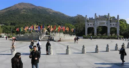 believer : Hong Kong, China - December 11, 2016: believer people and Buddhist monks at gateway of Po Lin Monastery of Big Buddha on background, symbol of Lantau Island, popular tourist destination. Time lapse