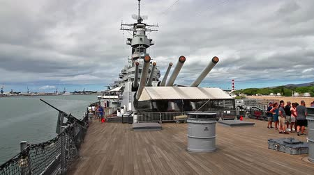 vezetett : HONOLULU, OAHU, HAWAII, USA - AUGUST 21, 2016: The prow with big canons of USS Missouri BB-63 warship at Pearl Harbor base. Commissioned in June 1944 for the World War II. Tourists in guided tour. Stock mozgókép