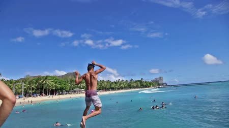 Оаху : Waikiki, Oahu, Hawaii - August 27, 2016: slow motion jumping from the Waikiki Pier between Kuhio Ponds and Queens Beach two sections of Waikiki Beach. On background.