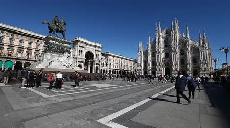 galleria vittorio emanuele ii : MILAN, ITALY- MARCH 7, 2017: panorama of Dome square with Duomo di Milano Cathedral in blue sky day. Tourists and Galleria Vittorio Emanuele II doorway with equestrian statue of Vittorio Emanuele II. Stock Footage