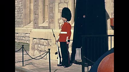 охранять : LONDON, UNITED KINGDOM - CIRCA 1979: Traditional British Royal Guard in red uniform standing at Tower of London castle. Historic restored footage on 1970s.