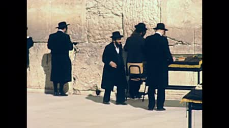 tallit : JERUSALEM, ISRAEL - CIRCA 1981: Jewish men in typical black dress and hat praying against the Western Wall in Old City of Jerusalem. Historic footage on 1980s in Israel.