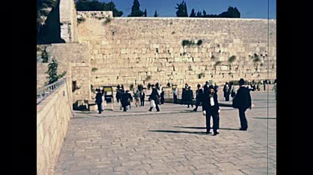tallit : JERUSALEM, ISRAEL - CIRCA 1981: tourists and Jewish men praying at Western Wall Plaza square, in Old City of Jerusalem. Historic footage on 1980s in Israel. Stock Footage