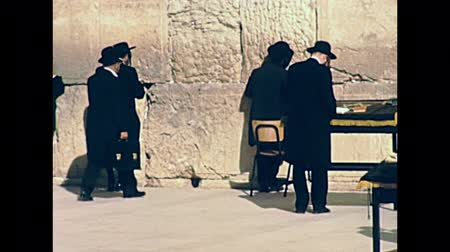 tallit : JERUSALEM, ISRAEL - CIRCA 1981: Western Wall of Jerusalem with Jewish men in black praying and kissing the Western Wall in Old City of Jerusalem. Historic footage on 1980s in Israel.