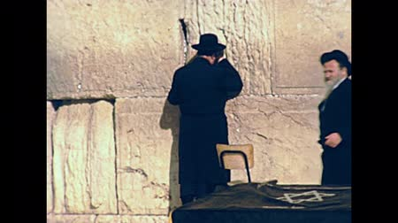 tallit : JERUSALEM, ISRAEL - CIRCA 1981: Jewish men in typical black dress and hat praying at Western Wall in Old City of Jerusalem. Historic footage on 1980s in Israel.