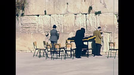 tallit : JERUSALEM, ISRAEL - CIRCA 1981: Jewish man in typical black dress and hat washing his hands at Western Wall Plaza square in Old City of Jerusalem. Historic footage on 1980s in Israel.