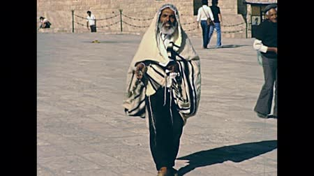 tallit : JERUSALEM, ISRAEL - CIRCA 1981: Senion Jewish man in typical talled shawl with prayer book in hand, walking in Old City of Jerusalem, Western wall square. Historic restored footage on 1980s in Israel.